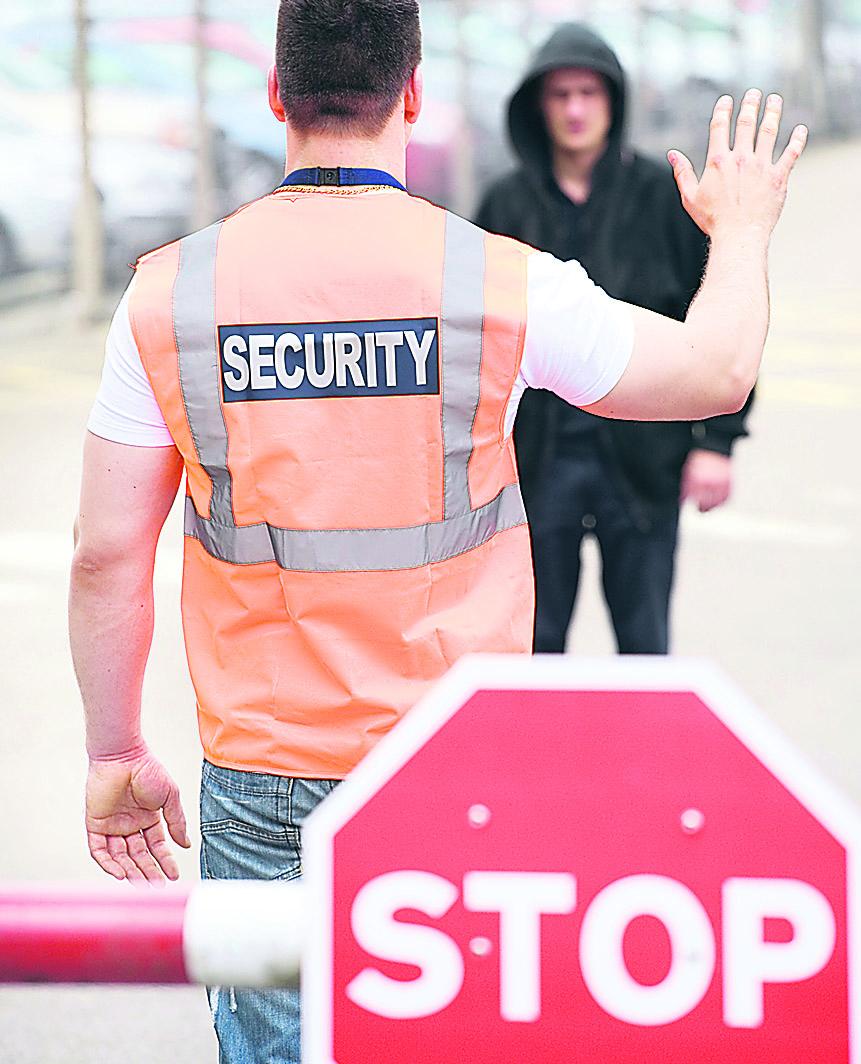 Ein Sicherheitsmann hält einen Menschen vor einem Bahnübergang auf. Online geht es um Datensicherheit im Internet