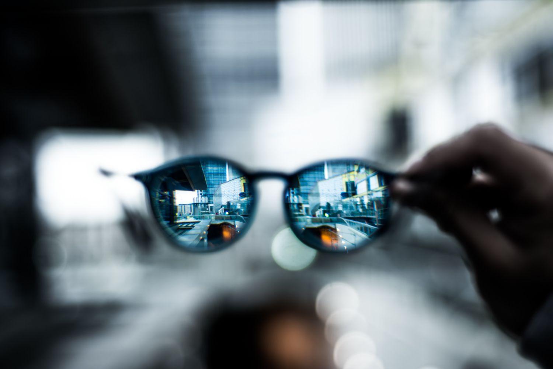 Jemand hält eine Brille in der Hand. Durchblick in Sachen Cyberpolicen und IT-Haftpflicht zahlt sich aus
