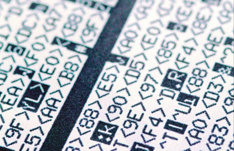 Detail eines mit Schrift- und Sonderzeichen bedruckten Papiers. Verschlüsselung ist in der Produktion ein wichtiges Thema