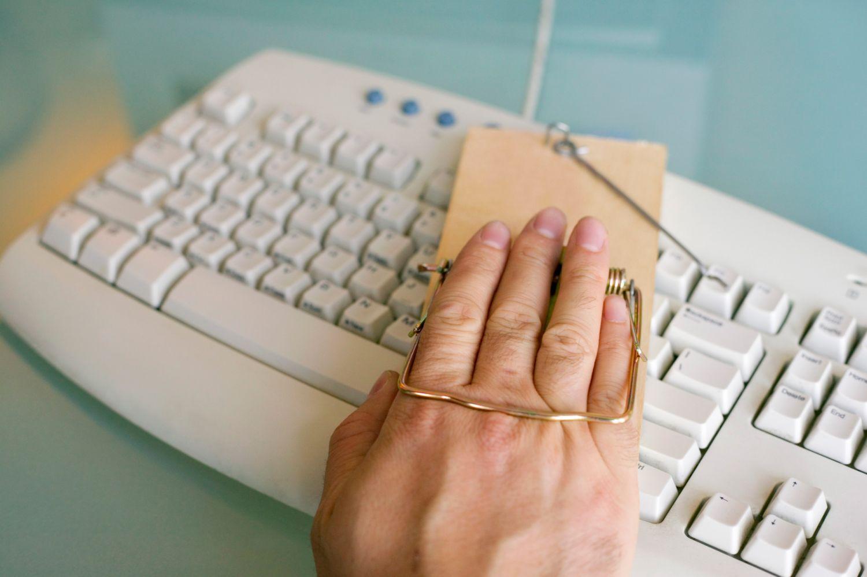 Eine Hand, die auf einer Computertastatur liegt, wird von einer Mausefalle umschlossen.
