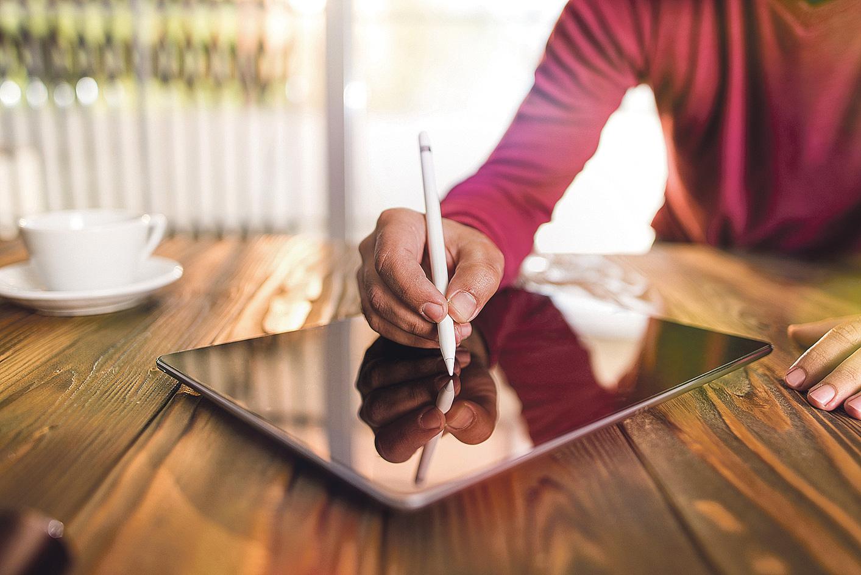 Eine Frau unterschreibt auf einem Tablet. Thema: elektronische Unterschriften
