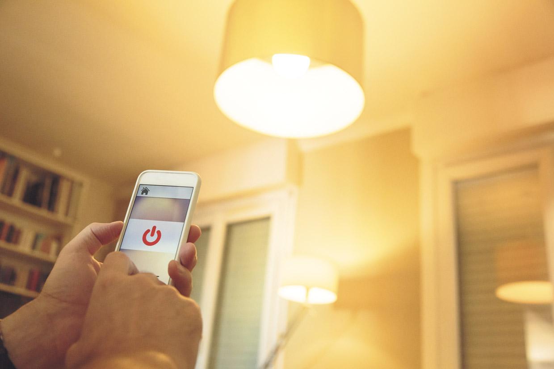 Smart Home: Jemand schaltet mit seinem Handy die Deckenleuchte an