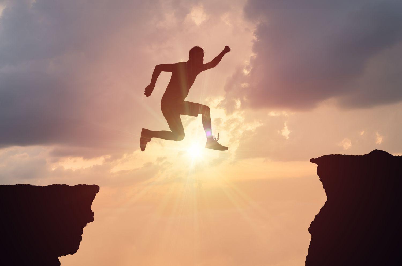 Eine Person springt von Klippe zu Klippe. Managementsysteme helfen, die Lücke zwischen Soll und Ist zu schließen