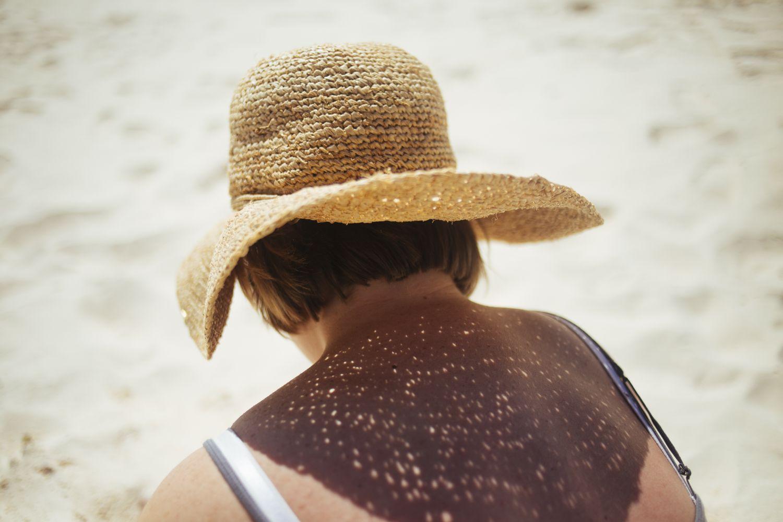 Eine Frau sitzt mit Sonnenhut am Strand. IT-Sicherheitstrends drücken aus, wo noch Schutz benötigt wird