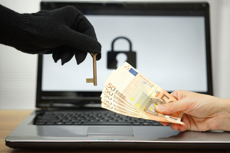 Ransomware: Die Hand eines Opfers bietet der Hand eines Erpressers mehrere 50-Euro-Scheine im Gegenzug für einen symbolischen Schlüssel zu gestohlenen Computerdaten.