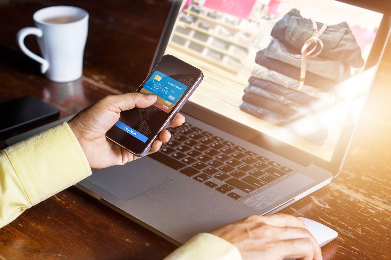 Eine Person bestellt mit ihrem Handy online Waren. Eine sichere Finanz- und Forderungs-IT wird zukünftig noch wichtiger