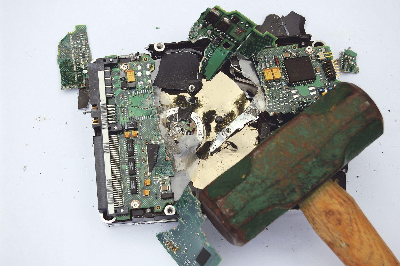 Datenlöschung auf die grobe Art: Auf einer zertrümmerten Platine liegt ein Hammer