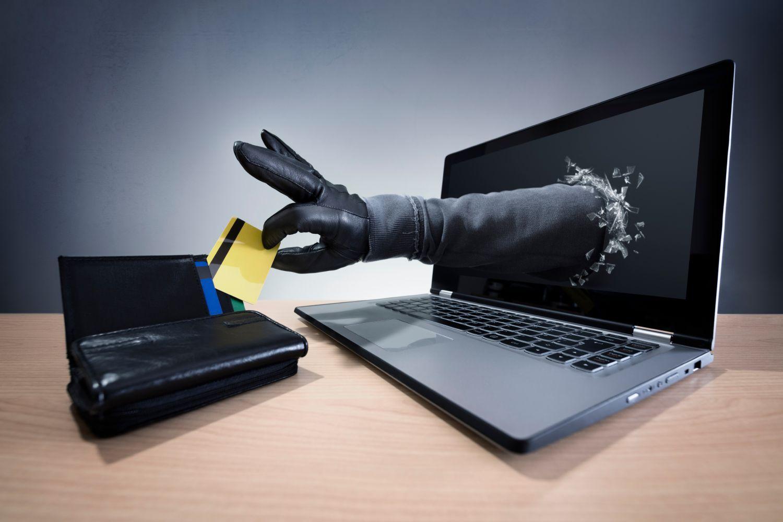 Prävention in der IT-Sicherheit heißt, Unternehmen vor Datenklau rechtzeitig schützen. Eine Hand greift aus einem Laptopbildschirm in ein Portmonee