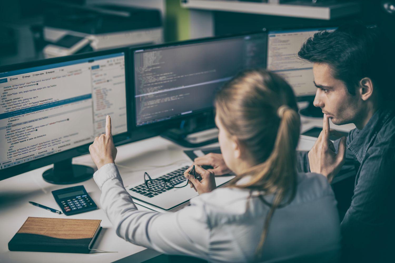 Zwei Mitarbeiter am PC. Datenschutz in Unternehmen ist ein hochrelevantes Thema