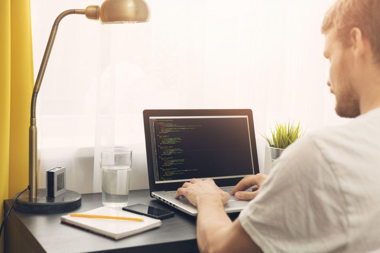 Junger Mann arbeitet von zuhause aus und kümmert sich um die IT-Sicherheit