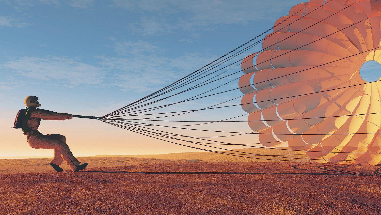 Thema IT-Versicherung: Eine Person zieht ihren Fallschirm durch die Wüste