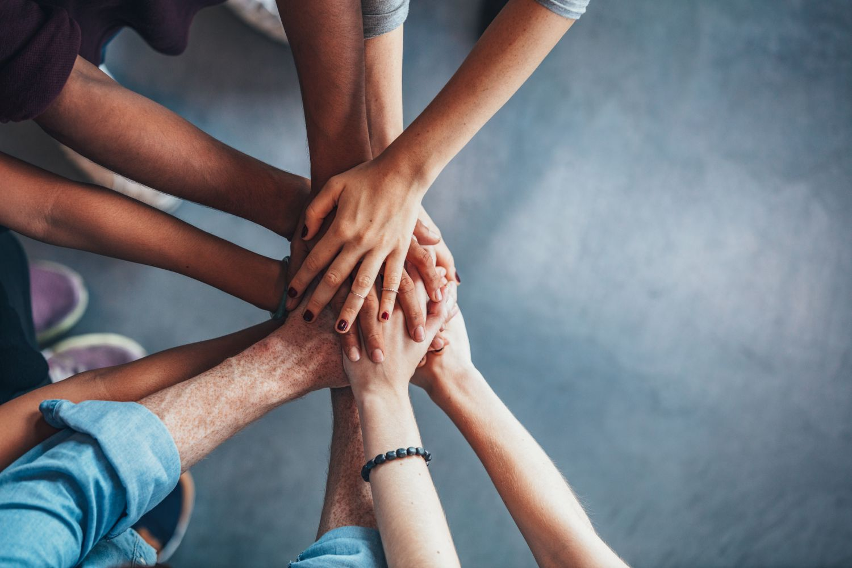 Eine Gruppe Menschen legt ihre Hände in der Mitte aufeinander. Symbolbild Compliance
