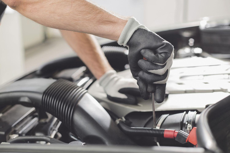 Ein Mechaniker schraubt an einem Auto. Ein Fuhrpark braucht eine leistungsstarke Flottenversicherung