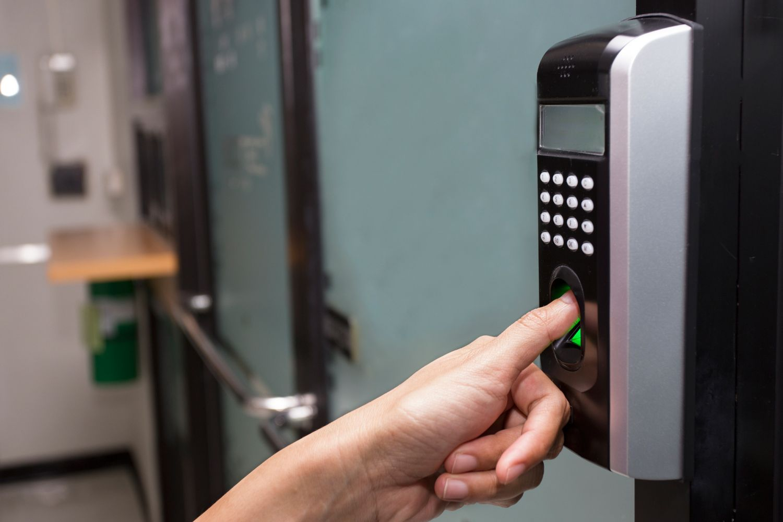 Jemand verschafft sich durch Fingerprint-Analyse Zutritt durch eine Tür.