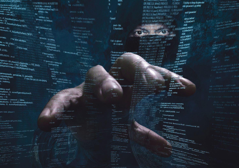 Ein Krimineller greift in einen Programmiercode. Thema: IT-Forensik
