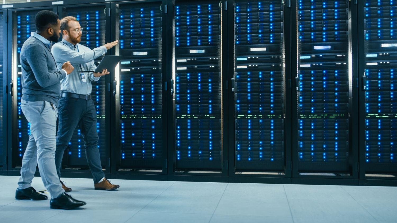 Zwei Mitarbeiter laufen an Servern vorbei