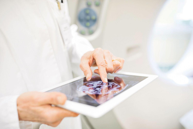 Eine Person hält ein Tablet mit einem Gehirnscan auf dem Bildschirm.