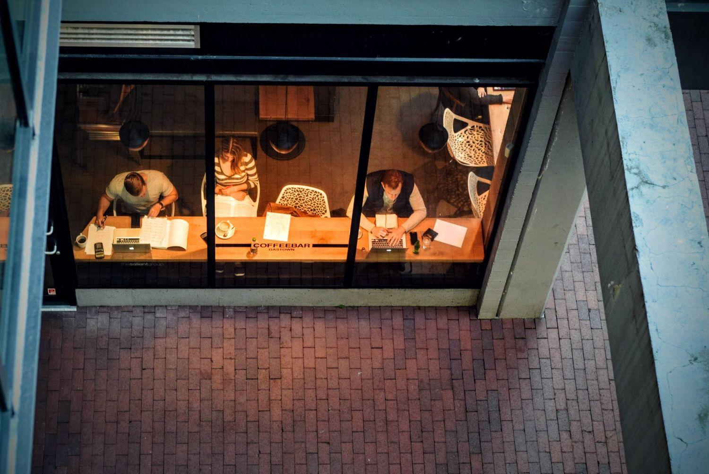 Blick auf an ihren Laptops arbeitende Menschen in einem Café. Beim Thema IT-Sicherheit in Unternehmen müssen Verantwortliche um die Ecke denken